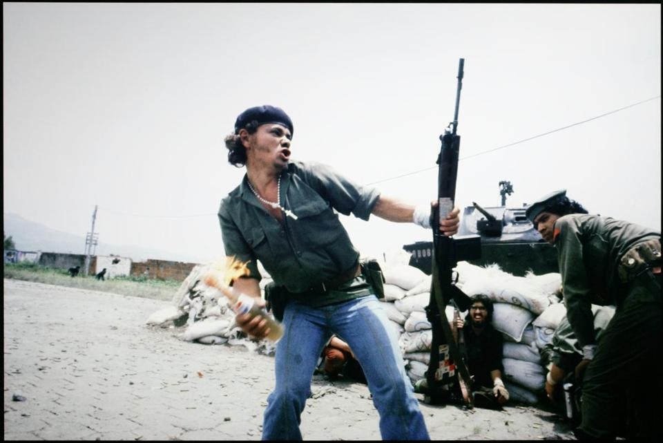 "A picture from the 1991 documentary film PICTURES FROM A REVOLUTION, directed by Susan Meiselas, Alfred Guzzetti, and Richard P. Rogers. Caption: Susan Meiselas, ""Sandinistas at the wall of the National Guard headquarters, Esteli, Nicaragua"" 19Documania"